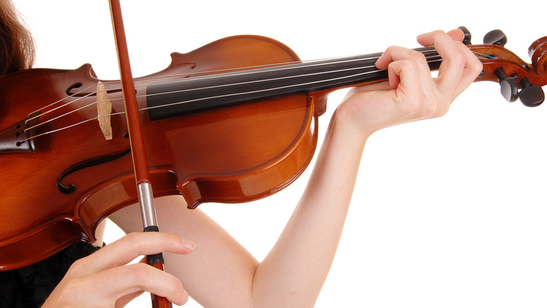A closeup picture of a woman playing the violin, isolated for whitebackground.