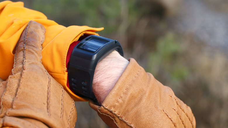closeup of hands and arm with sportwatch being paused during walk in forest